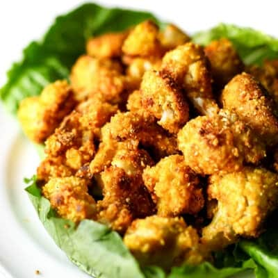 A white plate with a bed of lettuce and roasted cauliflower nuggets.