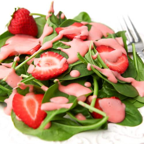 A white plate full of baby spinach and sliced strawberries with pink strawberry dressing drizzled over it.