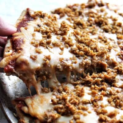 A pizza covered in vegan sausage crumbles made with TVP and spices.