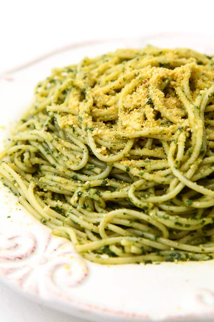 A white plate filled with spaghetti tossed in pesto and topped with vegan Parmesan cheese.