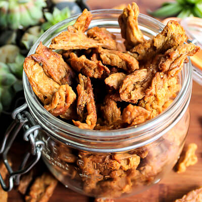 A glass jar filled with vegan jerky made with soy curls.