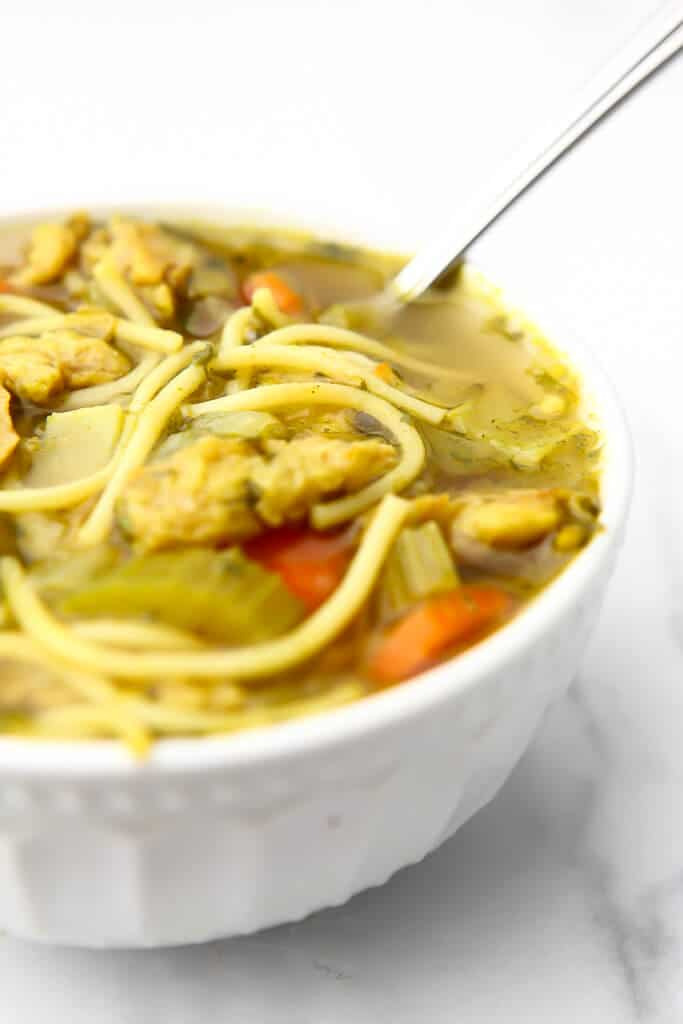 A white bowl filled with vegan chicken noodle soup with a spoon in it.