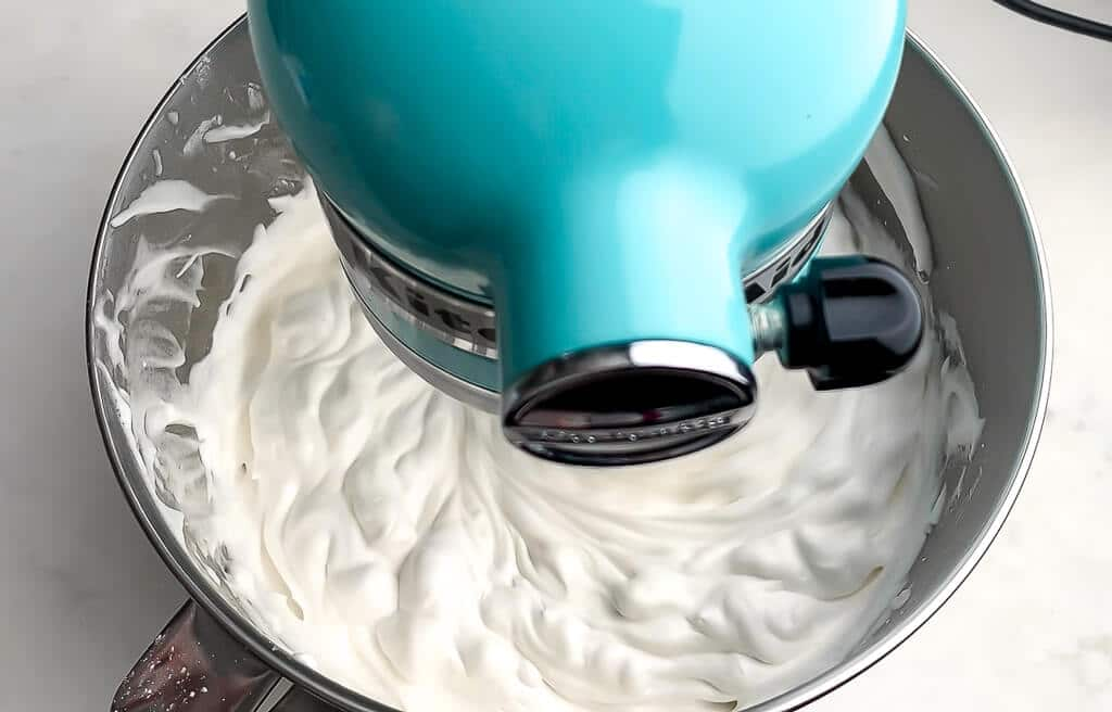 Vegan whipped cream being whipped in a blue kitchen aid mixer.