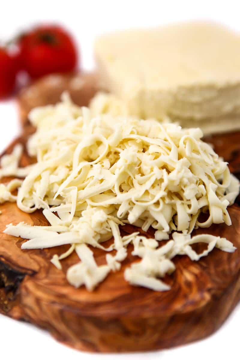 Vegan mozzarella cheese shredded on a wooden cutting board.