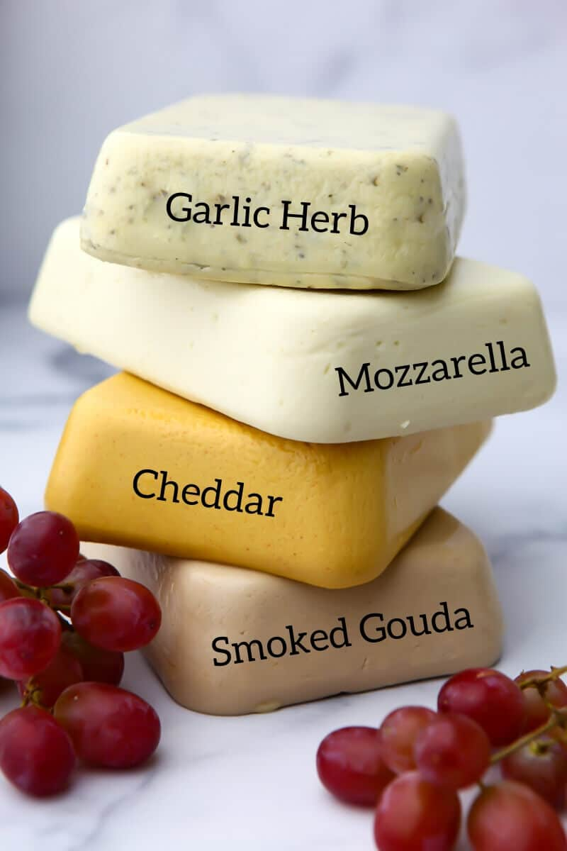 A stack of 4 types of vegan cheese that you can easily make including garlic herb, mozzarella, cheddar, and smoked Gouda.