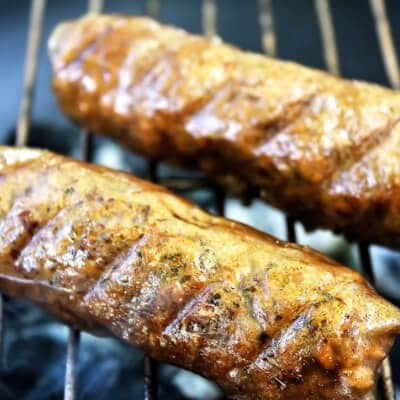 Two gluten free vegan sausage links cooking on a grill.