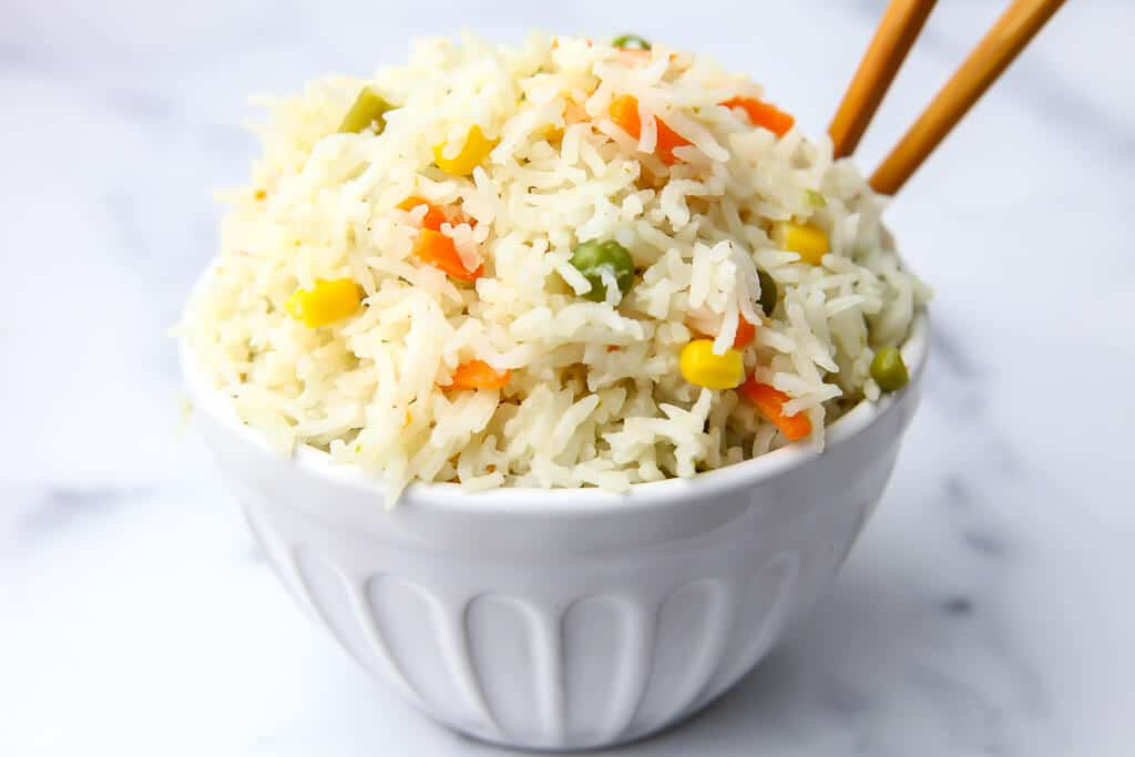 A white bowl filled with coconut rice with chop sticks in it.