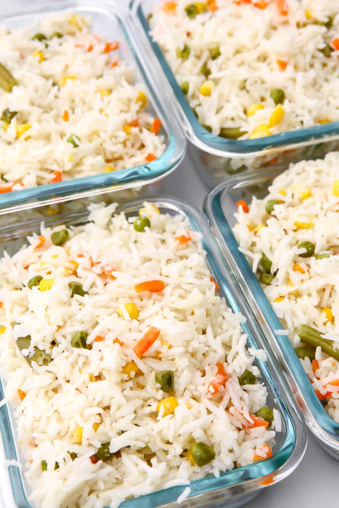 Four containers filled with Thai coconut rice to be store in the fridge or freezer for meal prep.