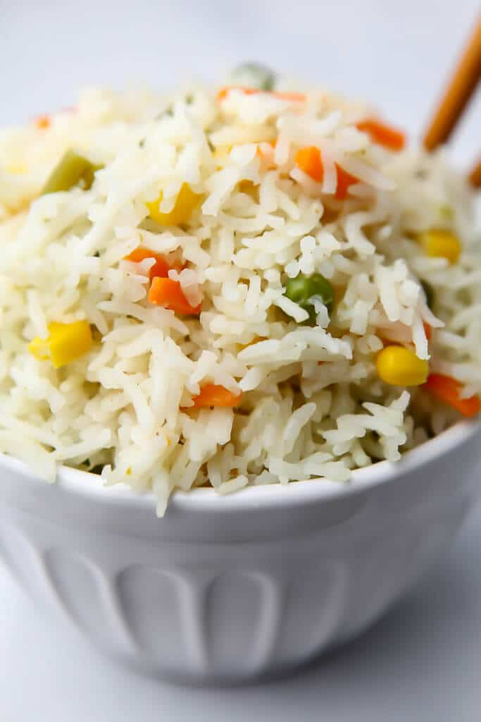 Thai curry coconut rice with vegetables in a white bowl.