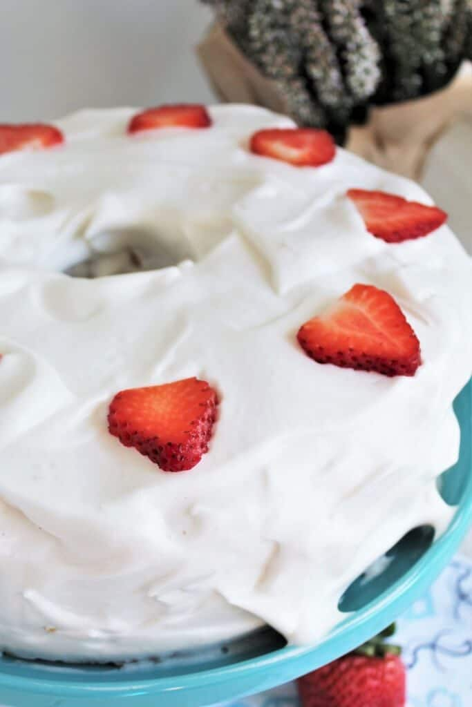 A finished vegan angel food cake topped with whipped cream and strawberries.
