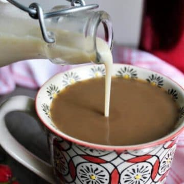 Homemade vegan coffee creamer made with soy milk being poured into a cup of coffee.