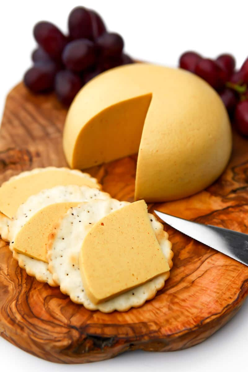 A wedge of vegan cheese on a wooden cutting board with some slices on crackers and red grapes behind it.