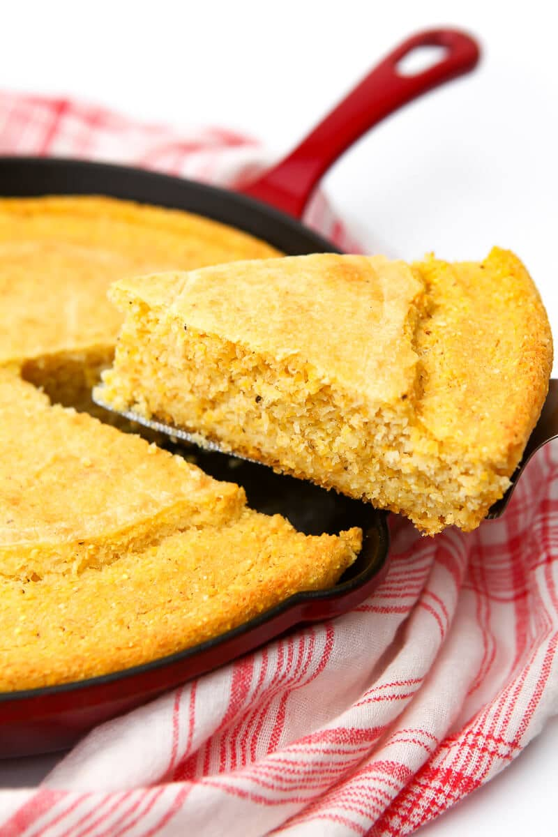 A slice of vegan skillet cornbread being taking out of a red skillet.