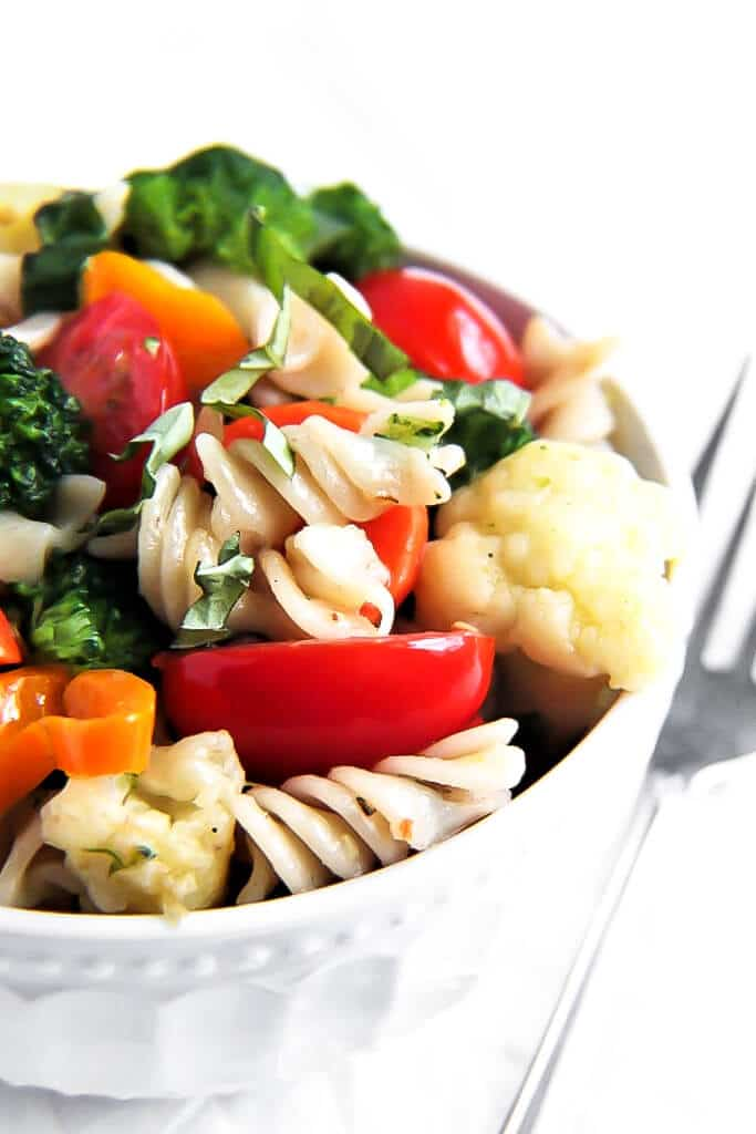 A bowl filled with gluten free vegan pasta primavera made with carrots, peppers, broccoli, cauliflower, and tomatoes.
