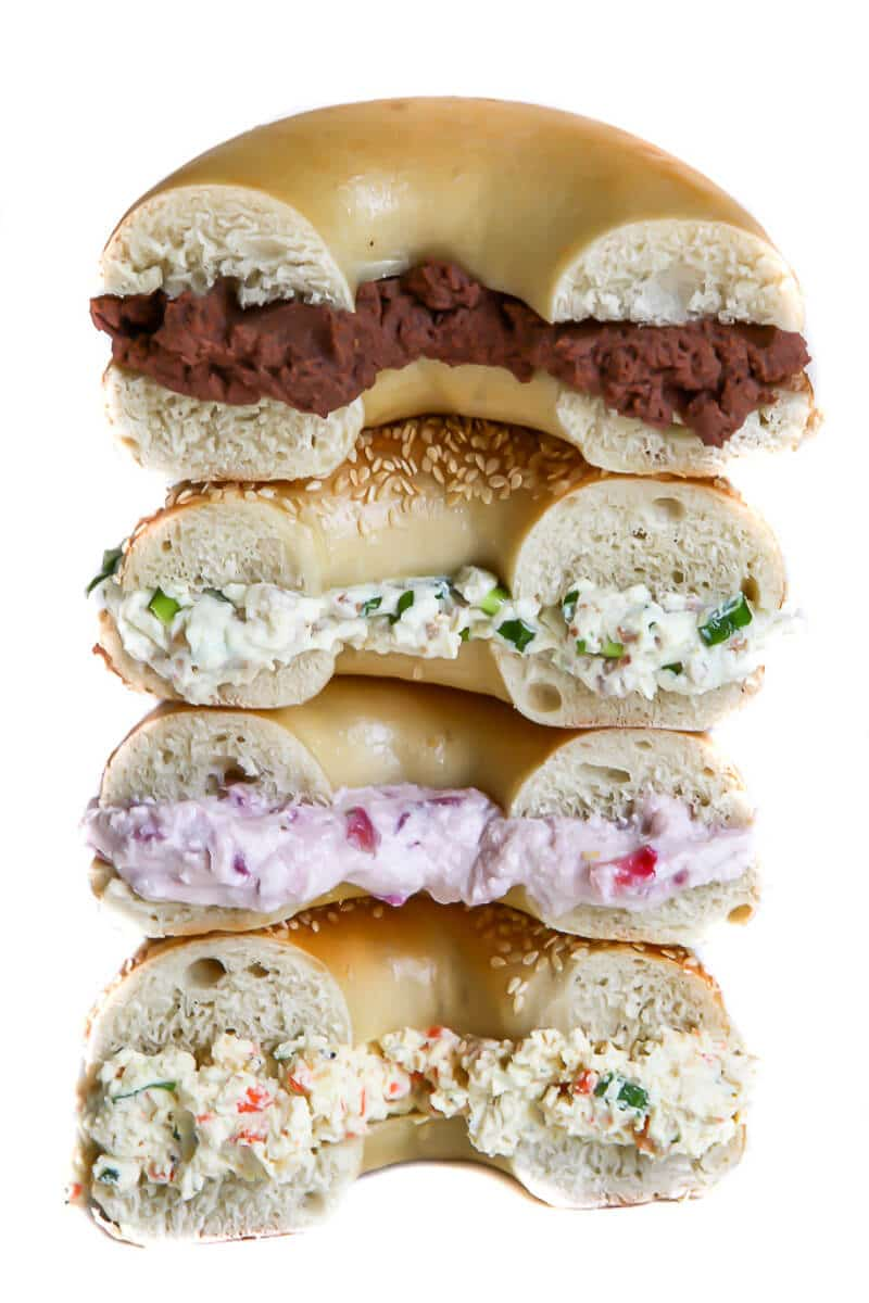 A stack of 4 bagels with 4 different flavors of vegan cream cheese including chocolate, bacon scallion, strawberry, and garden veggie cream cheese.