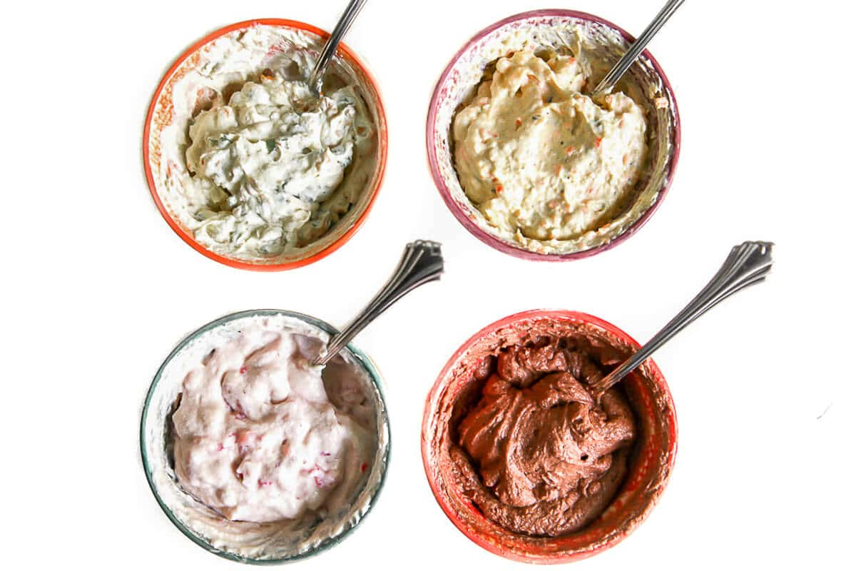 Four small colorful bowls with 4 different flavors of tofu cream cheese in them.