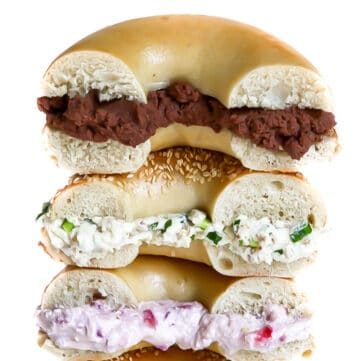 A stack of 3 bagels with 3 different flavors of vegan cream cheese including chocolate, garlic herb, and strawberry cream cheese.
