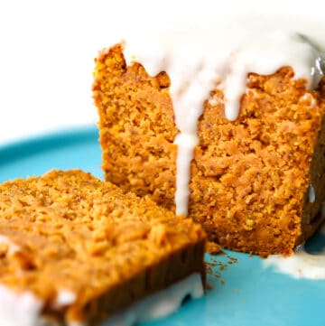 A loaf of vegan pumpkin bread with a slice cut off of it.