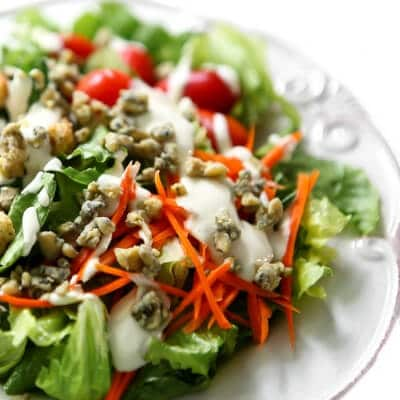 A salad with vegan blue cheese dressing and vegan blue cheese crumbles on top.