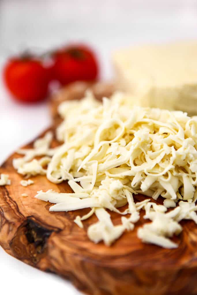 Shredded vegan mozzarella cheese on a wooden cutting board with two tomatoes behind it.