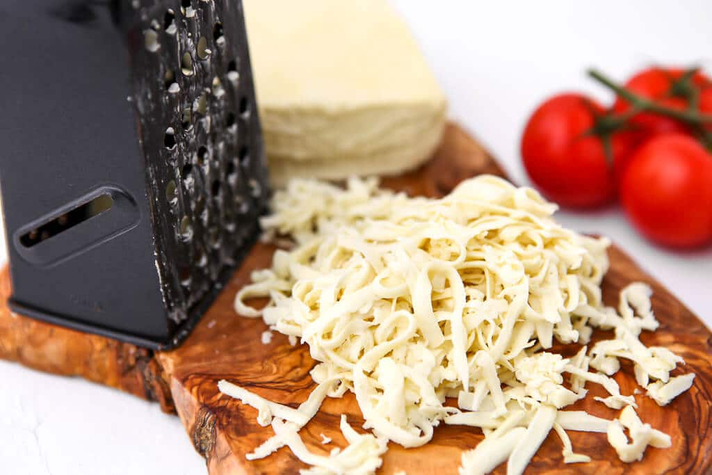 Vegan mozzarella cheese on a cutting board with a cheese grater and a tomato on the side.