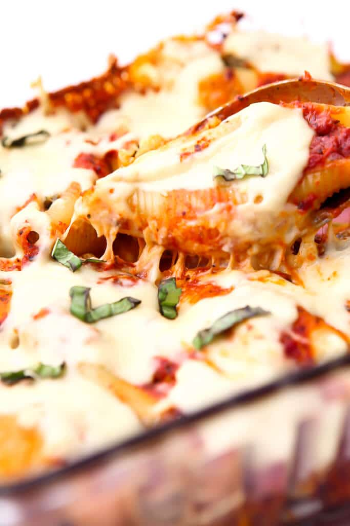Stuffed shells topped with vegan cheese that is melted and stretchy on top.