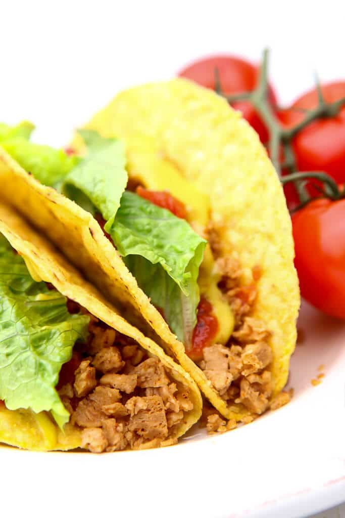 Vegan tacos made with TVP taco meat on a white plate with tomatoes on the side.