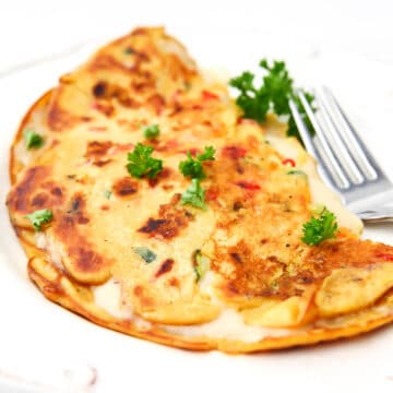 A chickpea omelette made with chickpea flour and veggies with vegan cheese inside.