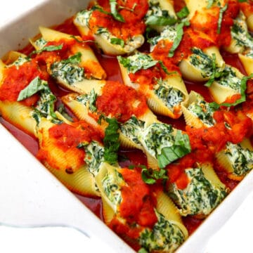 A baking dish filled with vegan stuffed shells made with tofu ricotta and spinach.