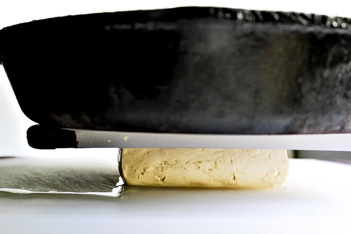 A cutting board and an iron skillet on top of a block of tofu to press the liquid out of it.
