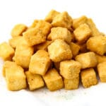 Crispy deep fried tofu cubes on a paper towel.