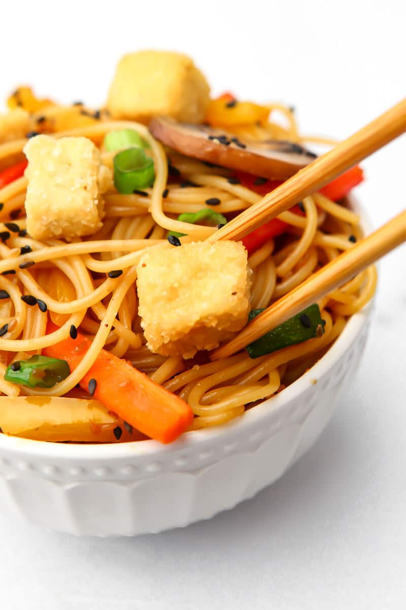 A bowl of teriyaki noodles with deep fried tofu cubes on top with chopsticks holding a cube of fried tofu.