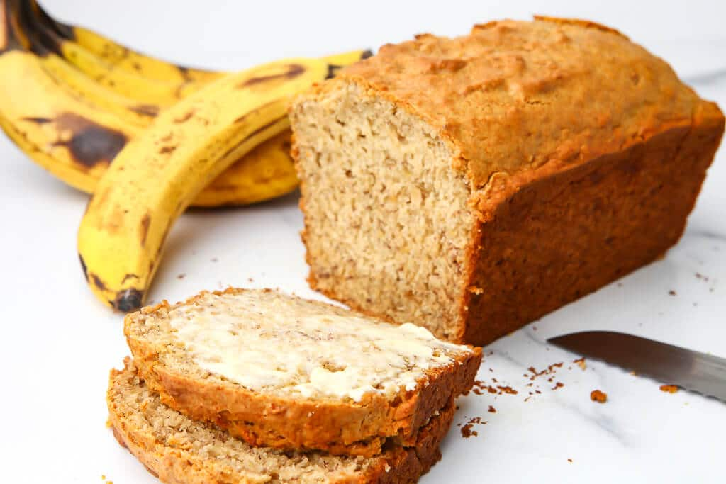 Vegan banana bread on a marble counter top sliced with some bananas behind it.
