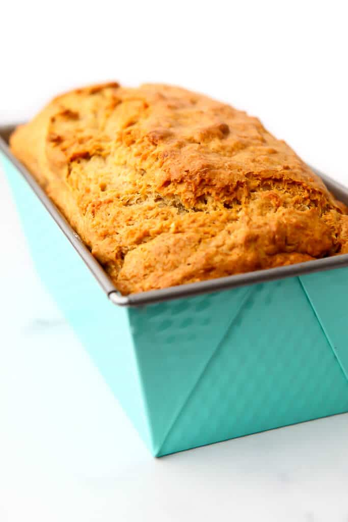 Golden brown baked banana bread in a bright blue loaf pan.