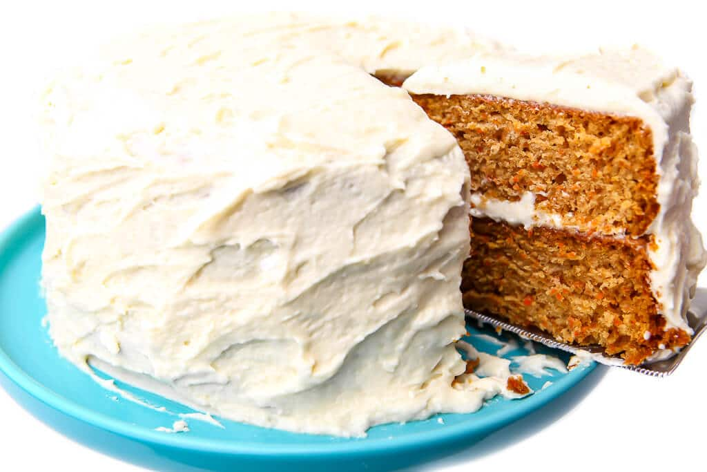 A piece of vegan carrot cake being taken out of a full cake on a blue cake stand.
