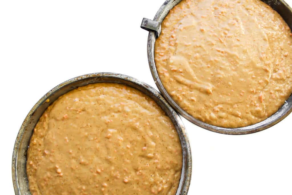 Two cake pans filled 3/4 of the way full with vegan carrot cake batter.