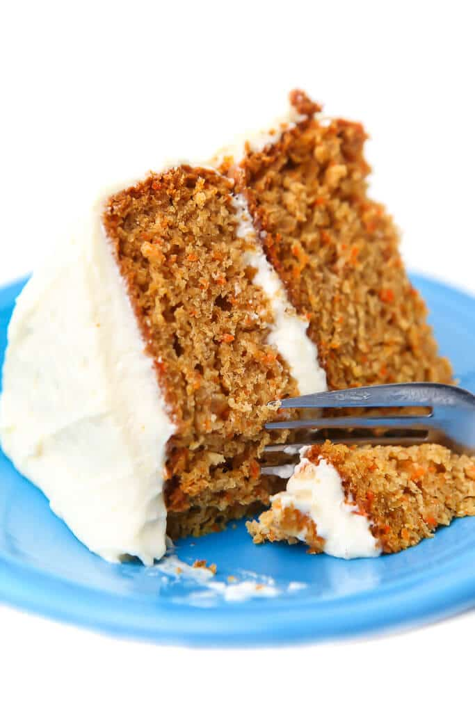 A slice of a vegan carrot cake with vegan cream cheese frosting with a fork cutting off a piece.
