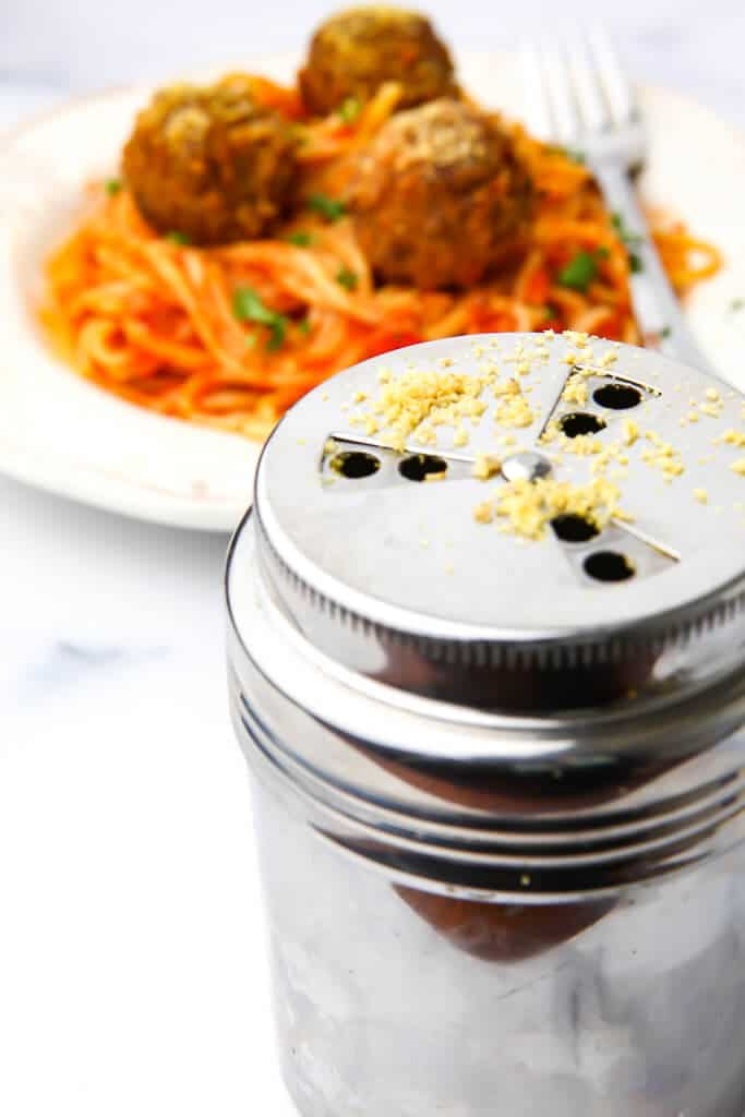 A Parmesan cheese shaker filled with vegan Parmesan in front of a plate of spaghetti and meatballs.