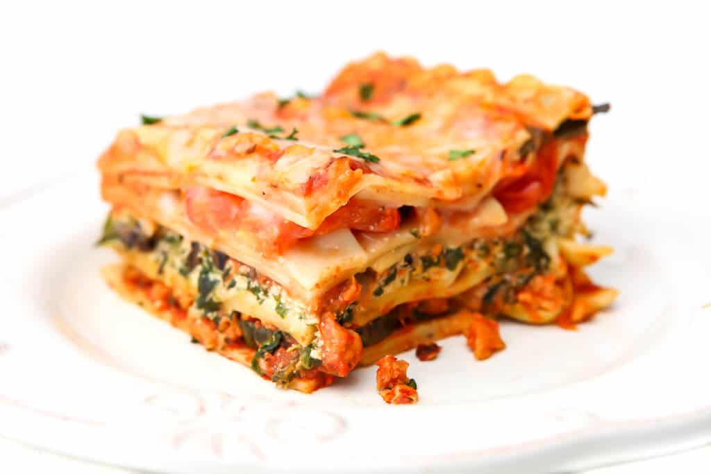 A piece of vegetarian lasagna with layers of tofu ricotta, spinach, tomatoes and vegan cheese.