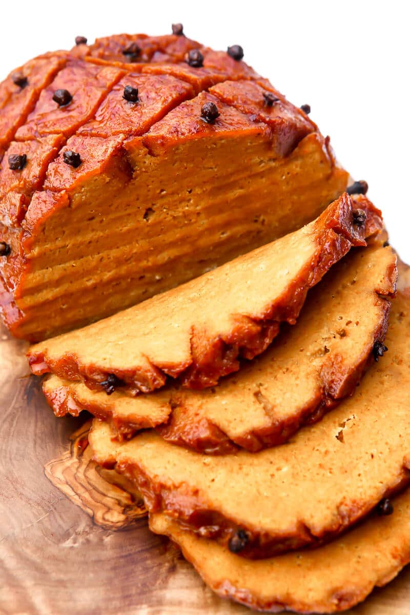 A top view of a vegan ham cut into slices on a wooden cutting board.