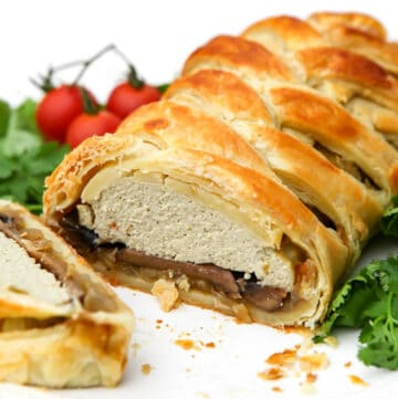 A vegan wellington filled with onions, mushrooms, and tofu on a white plate with a slice cut out of it.