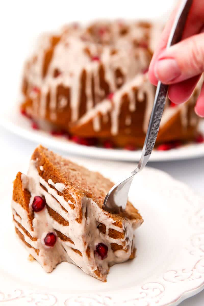A piece of bundt cake on a white plate with a fork in it with a full cake behind it.