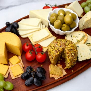A vegan cheese board filled with a variety of vegan cheeses, cherry tomatoes, olives, and grapes.