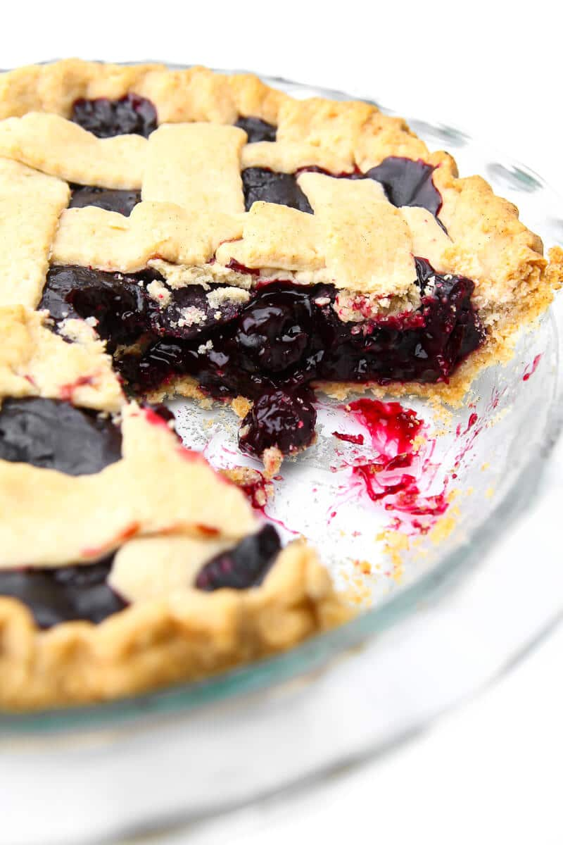 A vegan cherry pie with a lattice top and a piece taken out of it.