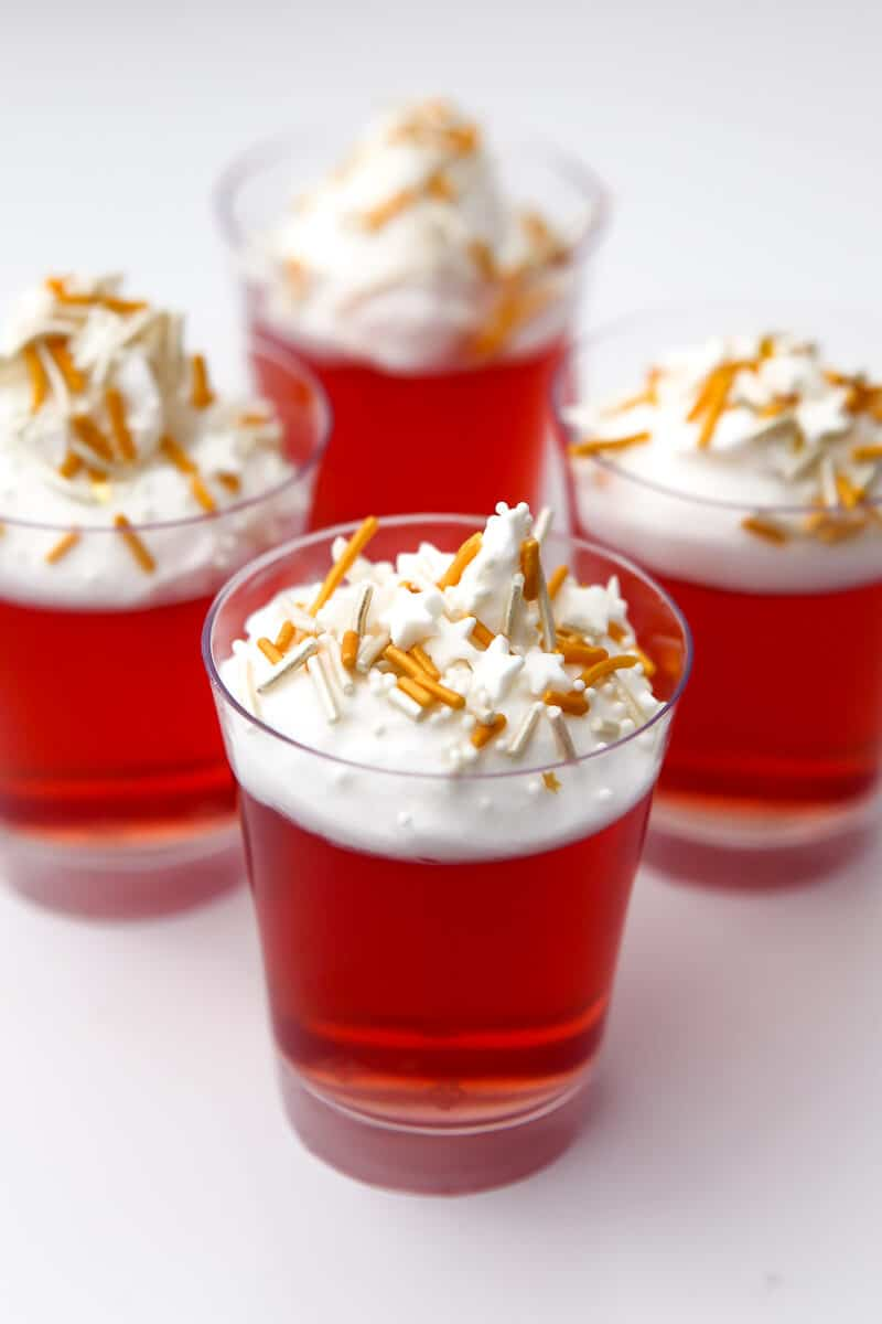 Four jello shots with vegan whipped cream and sprinkles on top.