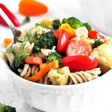 A bowl of easy vegan pasta primavera with broccoli, carrots, cauliflower, and tomatoes.