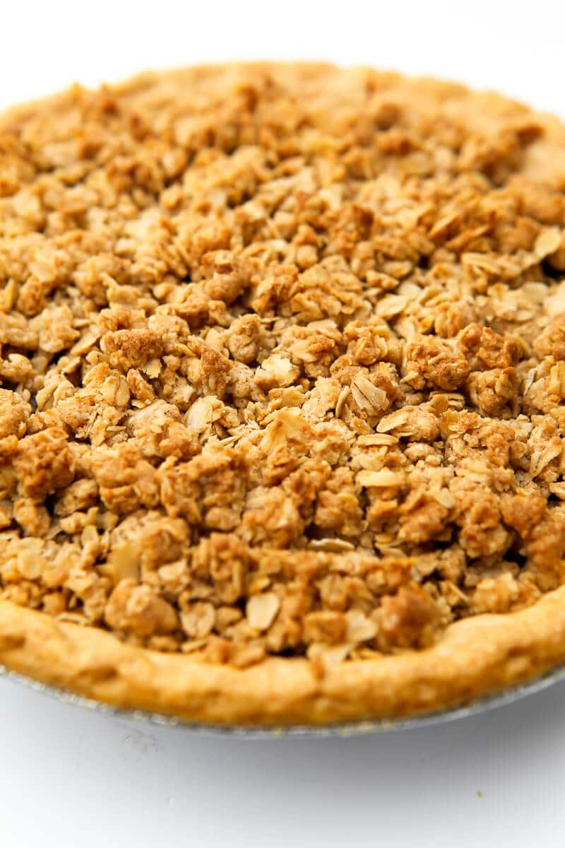 A cherry pie with a vegan crumble topping on a white countertop.