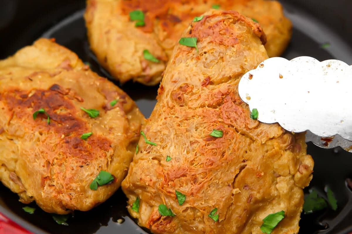 Vegan chicken breasts in a frying pan.