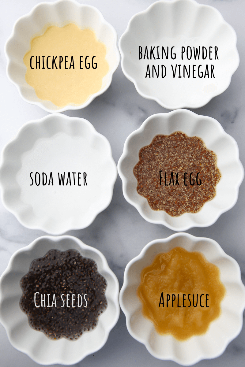 Six small white bowls with different types of egg replacements that you can use in baking with each labeled including chickpea egg, baking soda and vinegar, carbonated water, flax egg, chia seed egg, and apple sauce.