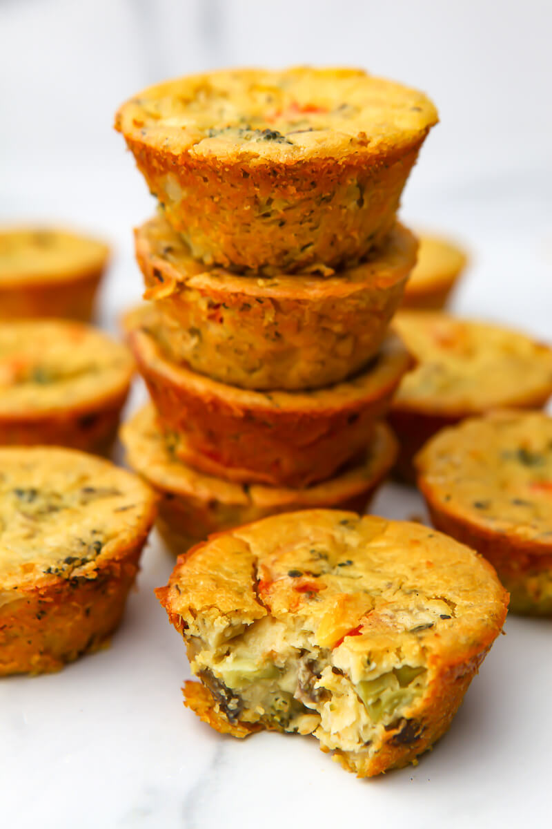 Vegan egg cups stacked 4 high with one in the front with a bite taken out of it.